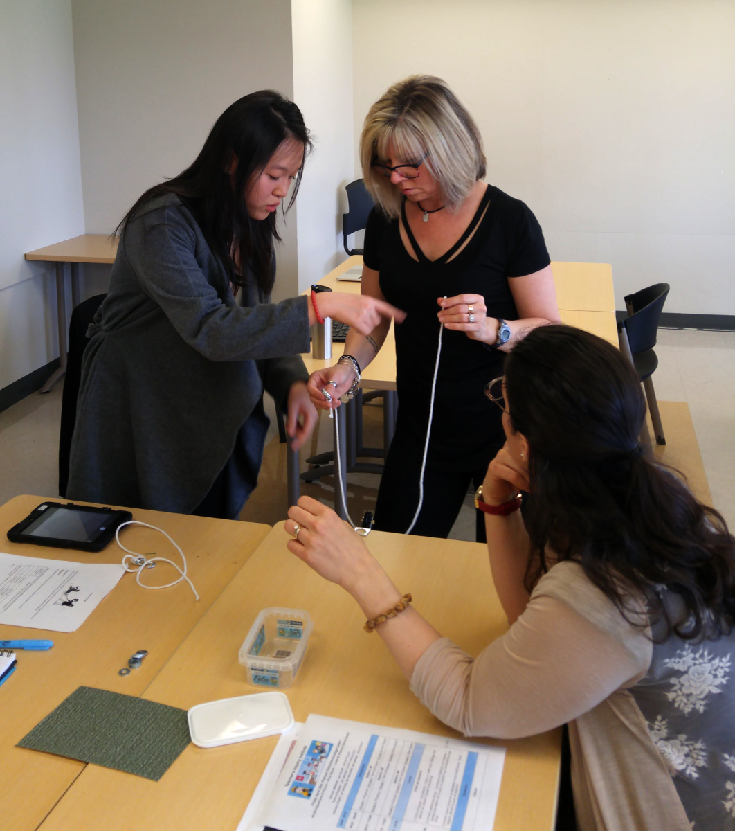 A McGill physics student shows teachers how to set up an experiment