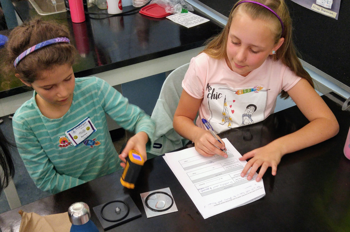Two children performing the heat and temperature experiment